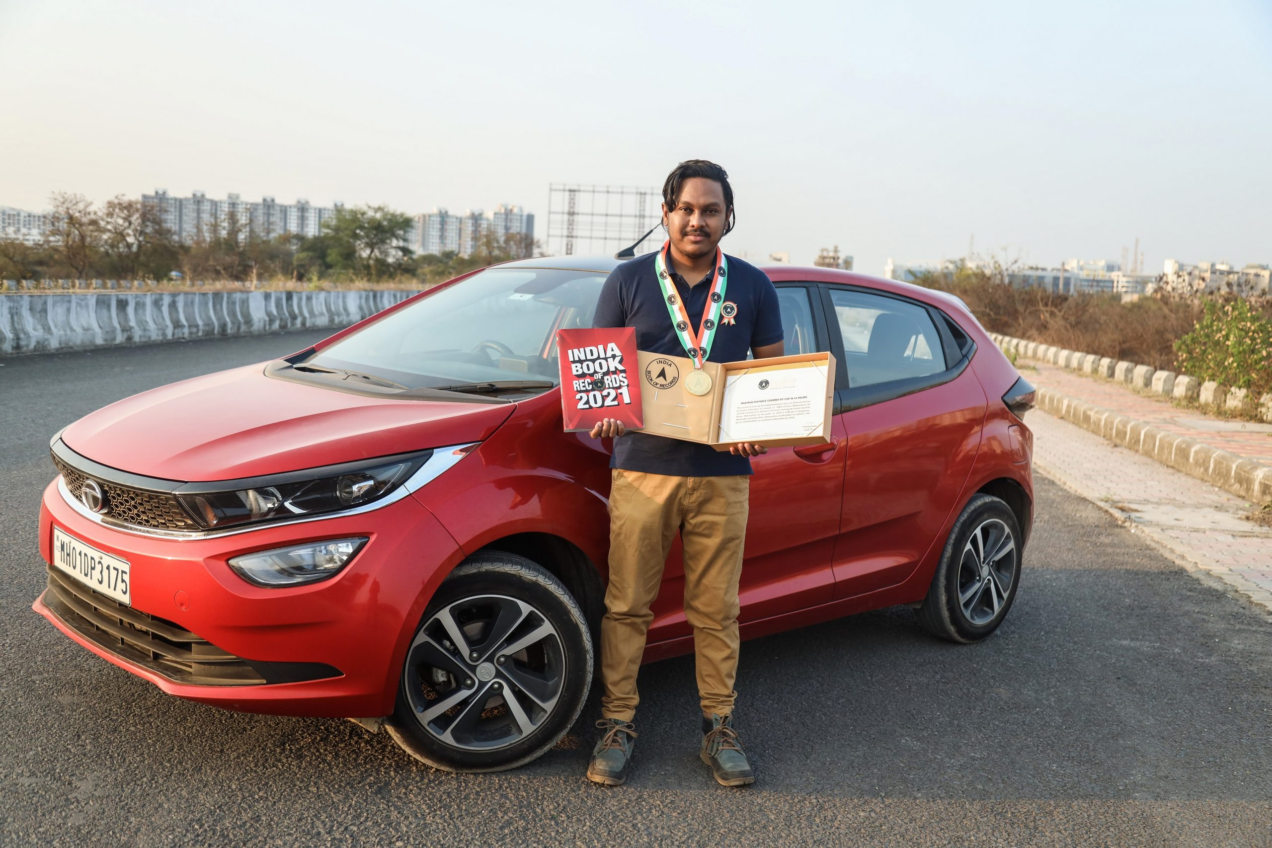 Devjit Saha along with the Tata Altroz post getting felicitated by The India Book of Records for covering the maximum distance recorded by a passenger car in 24 hrs